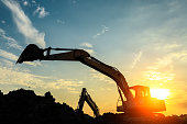 excavator working on construction site and sunrise natural landscape