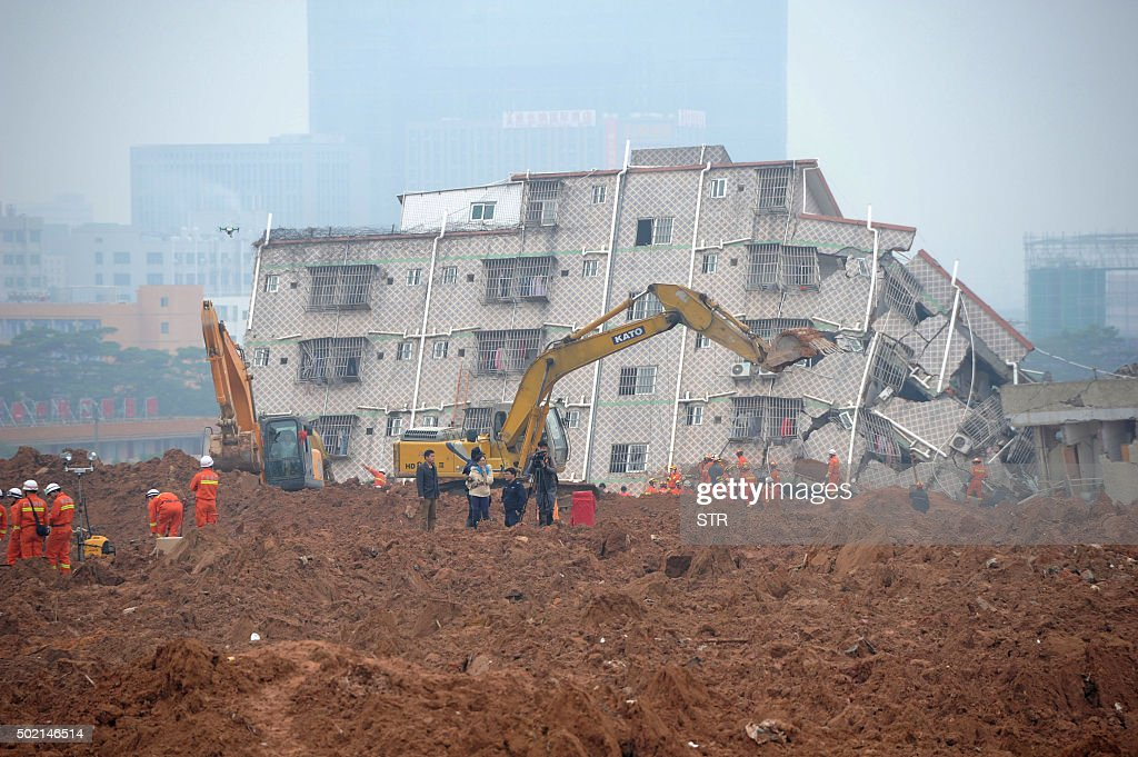 TOPSHOT Excavators and rescuers are seen working at the site of a landslide that hit an industrial park in Shenzhen south China's Guangdong province...
