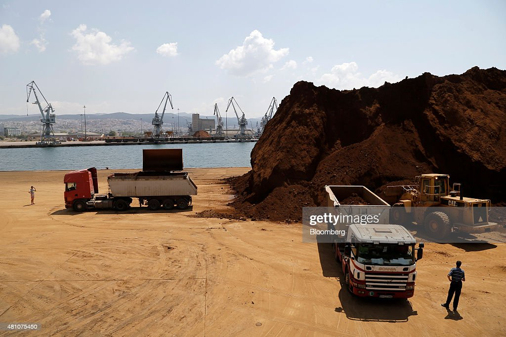 Excavators load trucks with unprocessed nickel ore on the dockside at Thessaloniki port operated by Thessaloniki Port Authority SA in Thessaloniki...