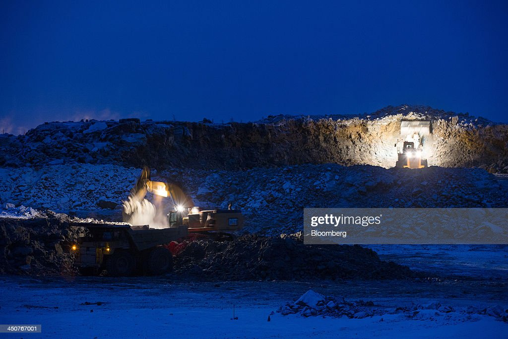 Excavators operate at night using electric lights to illuminate the diamond rock in the open pit at the Nyurbinsky diamond mine operated by OAO Alrosa in Nakyn, Russia, on Friday, Nov. 15, 2013. OAO Alrosa, the world's largest diamond producer, raised about $1.3 billion in an oversubscribed share sale from investors including Oppenheimer Funds Inc. and Lazard Ltd.'s asset-management unit, First Deputy Prime Minister Igor Shuvalov said. Photographer: Andrey Rudakov/Bloomberg via Getty Images