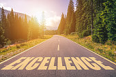 Excellence word written on road in the mountains