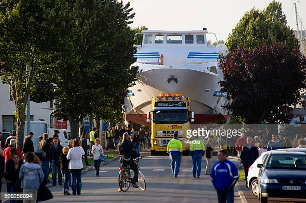 Exceptional haulage highspeed passenger ferry 'Jolie France' transported by road in the streets of Granville from the boathouse where it was built to...