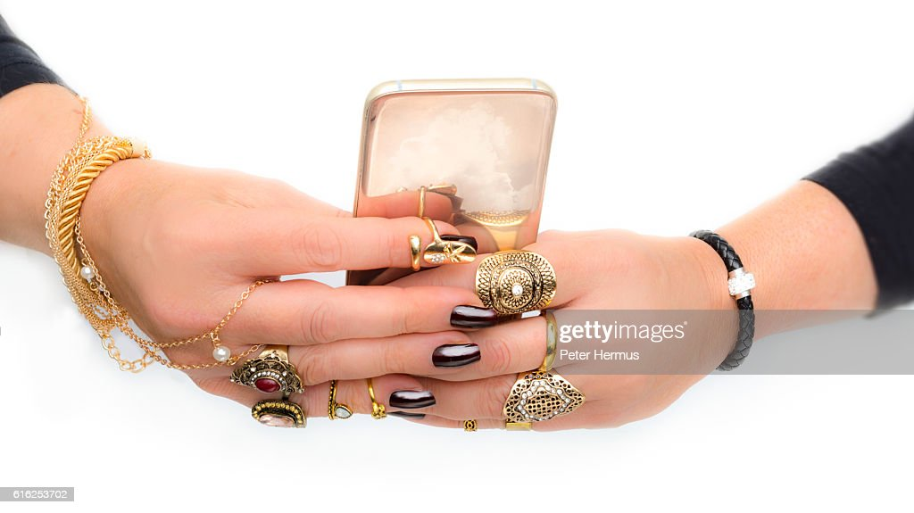 excessive jewelry hands with dark nails and gold smartphone : Stock Photo