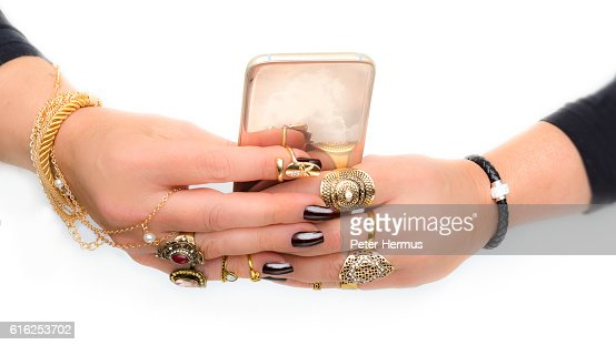 excessive jewelry hands with dark nails and gold smartphone : Foto de stock