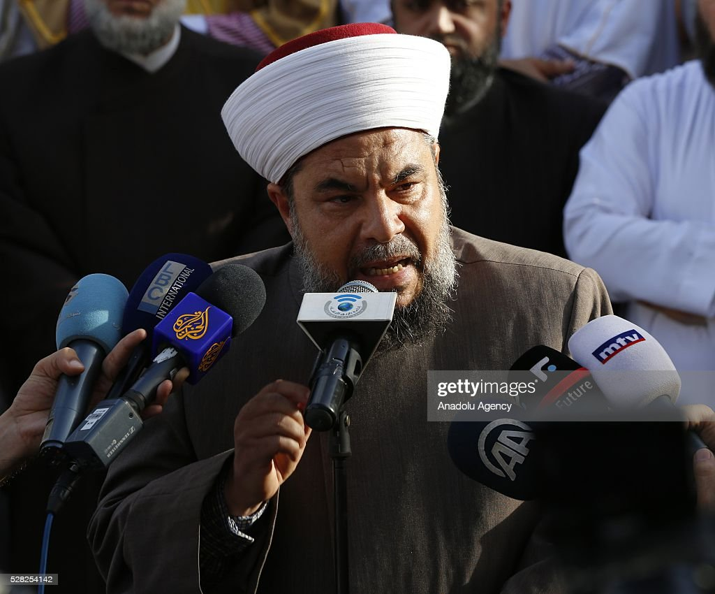 Ex-chairman and board member of Lebanon's Muslim Scholars Committee Sheikh Salim Er-Rifai delivers a speech as a group of Muslim scholars hold signs reading in 'Aleppo is burning, Help Aleppo' and protest against the air strikes conducted by the Assad regime and Russia over the Aleppo in front of Russian embassy building in Beirut, Lebanon on May 4, 2016.