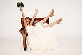 Excitable bride in armchair, cheering