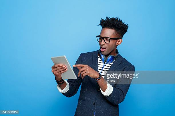 Excited afro american guy in fashionable outfit, holding digital tablet