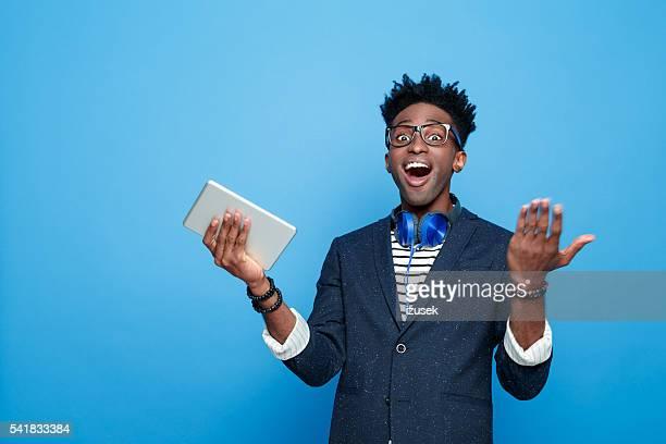 Heureux jeune afro-américaine en tenue à la mode, tenant la tablette numérique