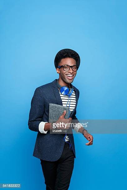 Excited afro american guy in fashionable outfit, holding notebook