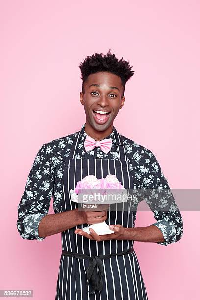 Excited afro american small business owner holding cookies