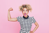 Studio portrait of excited afro american young woman flexing muscle. Pink background.