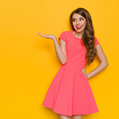 Smiling beautiful young woman in pink mini dress posing with hand on hip, presenting something and looking away. Three quarter length studio shot on yellow background.