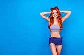Excited attractive girl with long ginger fair hair touch head with hands, wearing in short jeans shorts and smiling while standing on blue background
