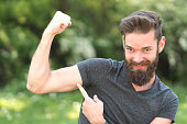 Excited bearded guy showing his biceps in park