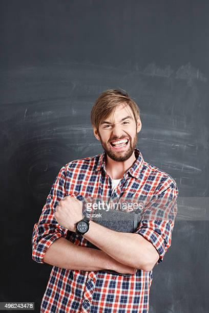 Heureux homme barbu souriant avec tableau noir