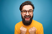 Excited handsome bearded man in glasses posing on blue background.