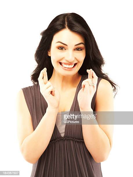 Excited beautiful young woman with fingers crossed