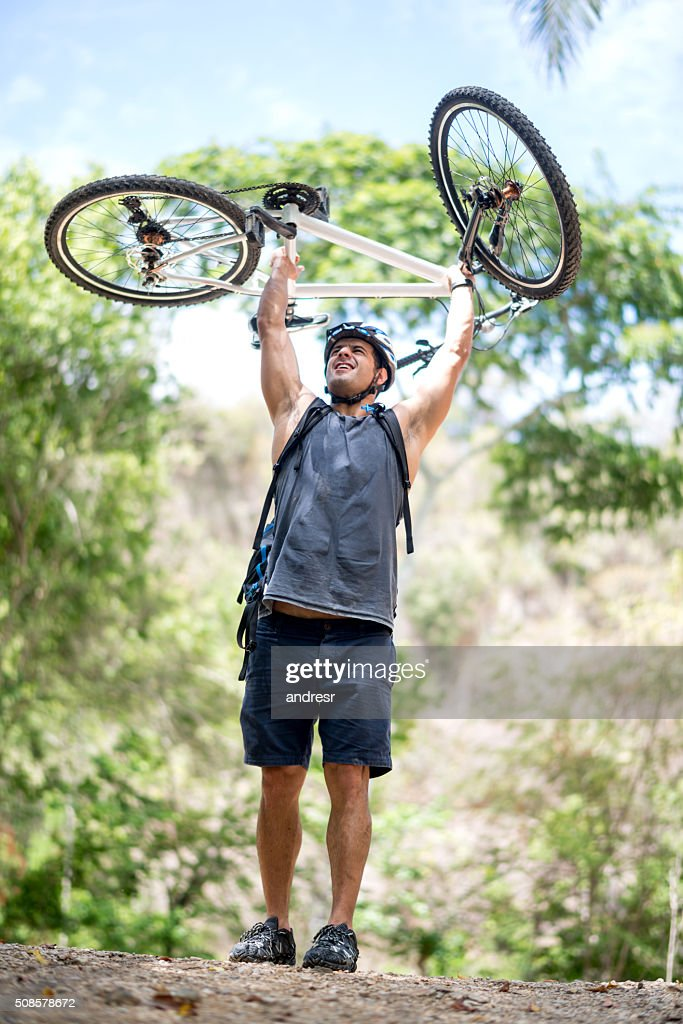 Excited biker achieving his goal : Stock Photo