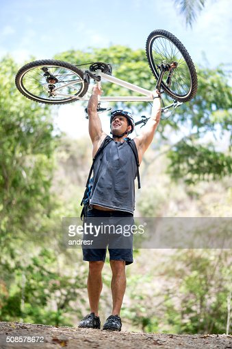 Excited biker achieving his goal : Stockfoto