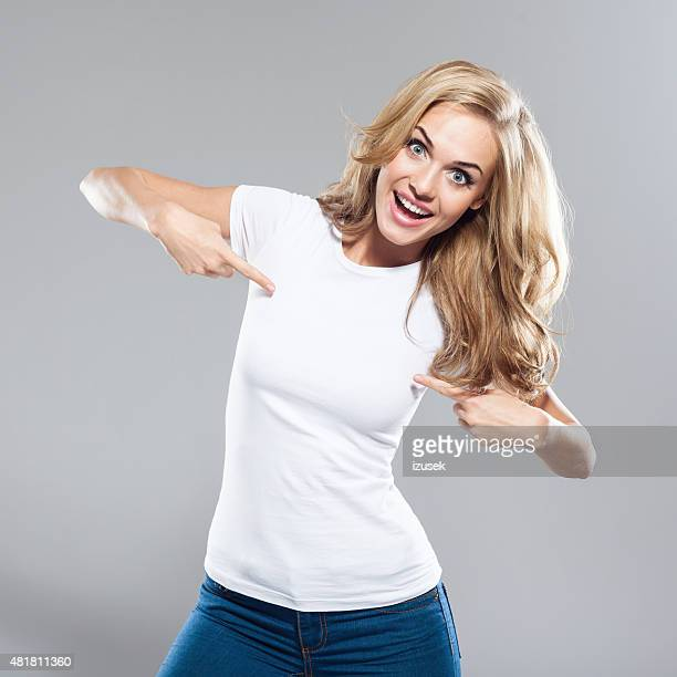 Excited blond hair young woman pointing at torso