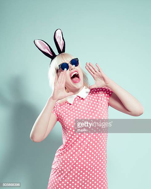 Excited blonde young woman wearing rabbit ears headband and sunglasses