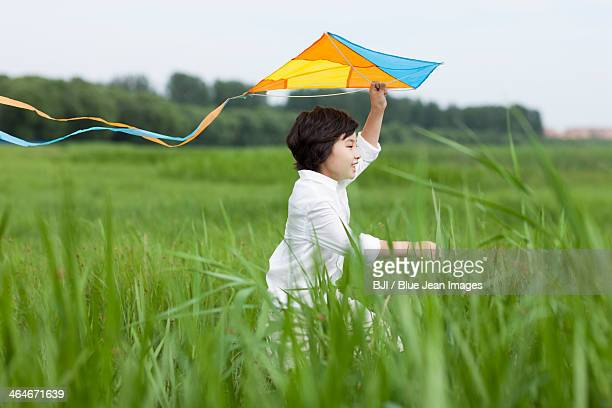 Excited boy flying a kite on the grass