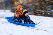 2 Excited Young Boys Share Sled Ride in Snow