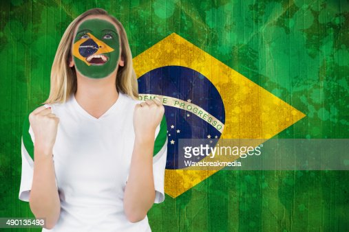 Excited brasil fan in face paint cheering : Stock Photo