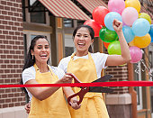 Excited business partners cutting ribbon on grand opening