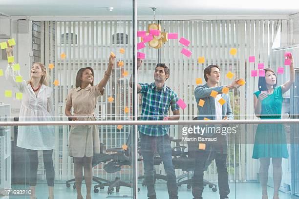 Une las personas de negocios con brazo en la ventana