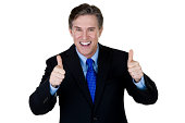 Excited businessman gesturing thumbs up