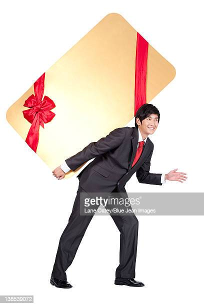 Excited Businessman Holding an Oversized Wrapped Card on His Back