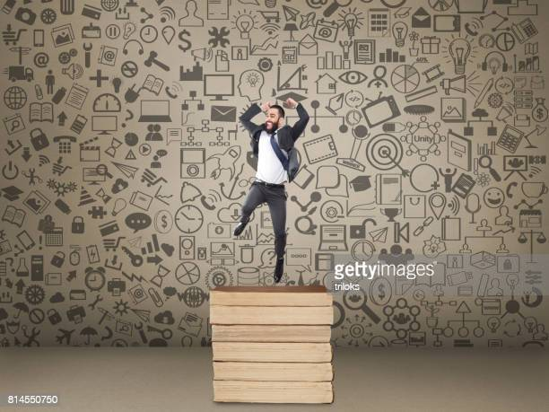 Excited businessman jumping over stack of books