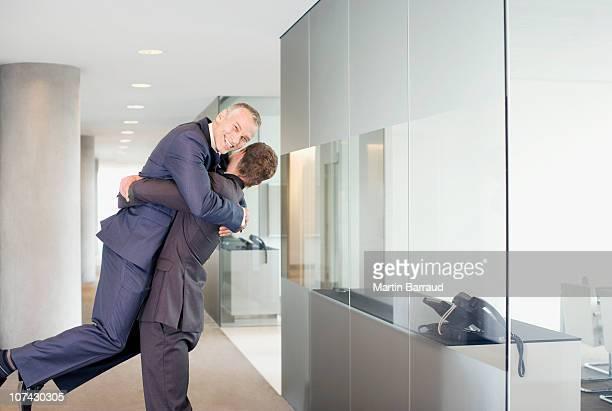 Heureux Homme d'affaires en levant collègue dans le couloir du bureau