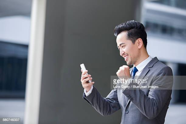 Excited businessman looking at smart phone