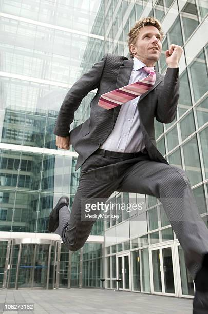 Excited Businessman Running Out of Office Tower