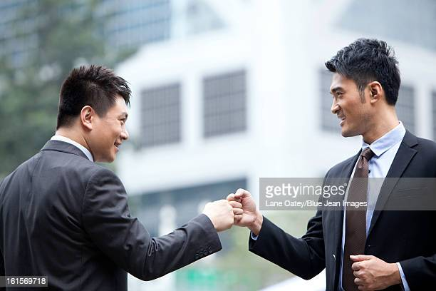 Excited businessmen celebrating and doing fist bump, Hong Kong