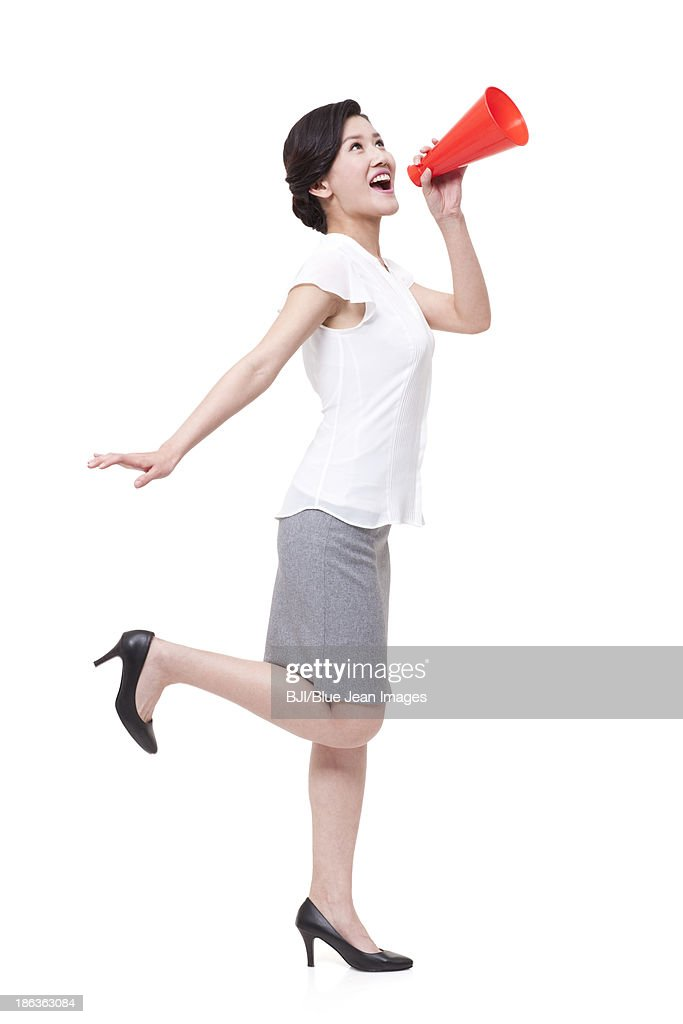 Excited businesswoman shouting with megaphone