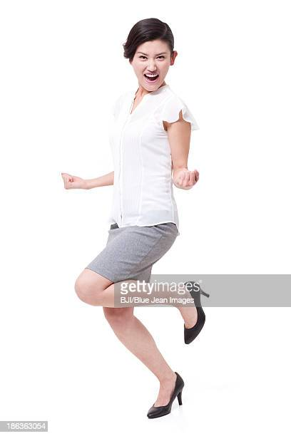 Excited businesswoman standing on one leg