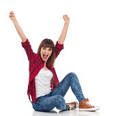 Excited young woman in red lumberjack shirt, jeans and brown sneakers sitting on a floor with arms raised and shouting. Full length studio shot isolated on white.