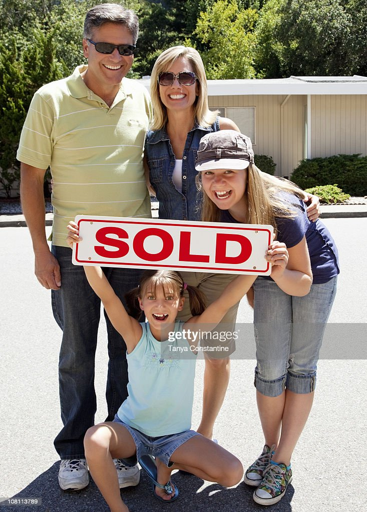 Excited Caucasian family holding ''sold'' sign