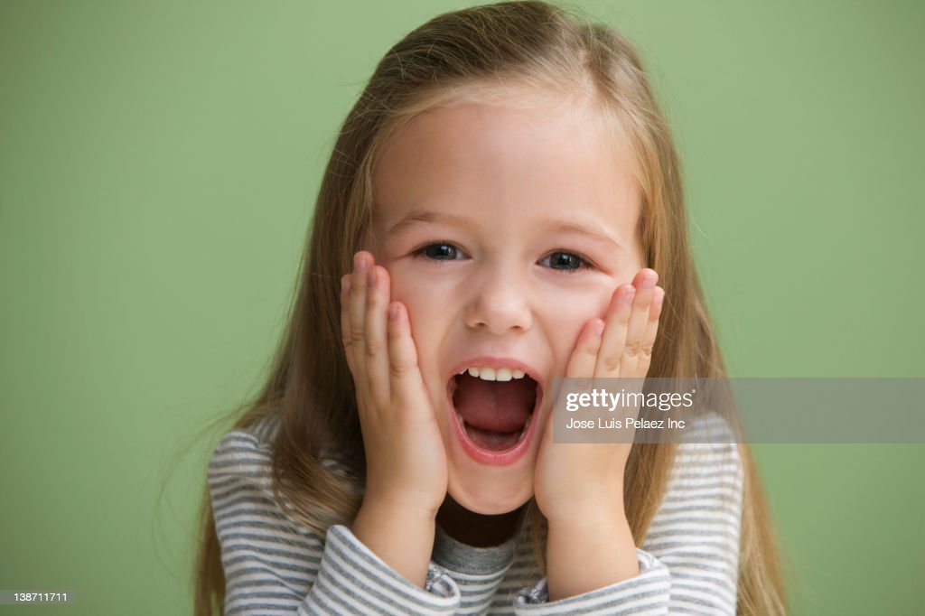 Excited Caucasian girl with head in hands : Stock Photo