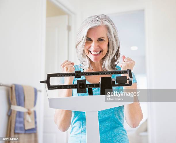 Excited Caucasian woman cheering on weight scale