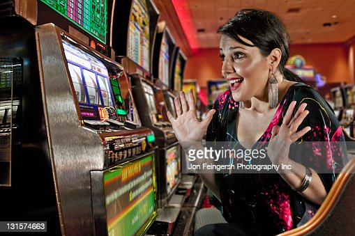 Excited Caucasian woman playing slot machines in casino : Stock Photo