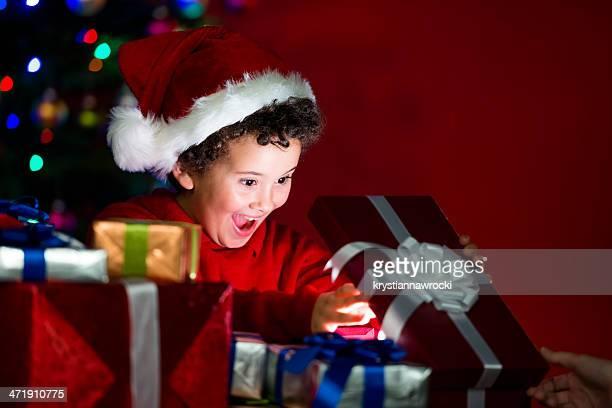 Heureux enfant ouvrant un cadeau sous le sapin de Noël