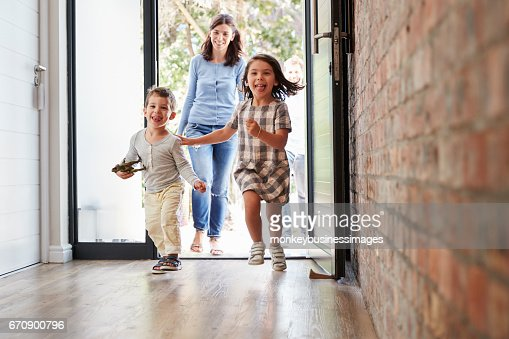 Excited Children Arriving Home With Parents : Foto de stock