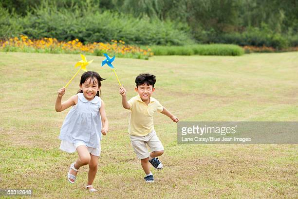 Excited children playing paper windmill
