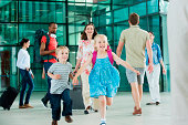 Excited children running on airport concourse