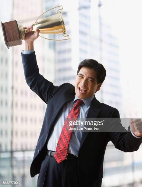 Excited Chinese businessman lifting trophy