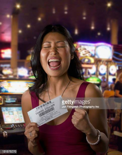 Excited Chinese woman holding gaming voucher in casino